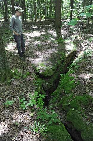 Preserve Manager Luke Mazza looks down at the jolly hole entrance to Bensons Cave on Tuesday, Aug. 19, 2014 in Howe's Cave, N.Y.  Bensons Cave, Schoharie County, NY,  was donated to the Northeastern Cave Conservancy (NCC)  by by the United States Cave Conservancy (USCC) on March 11, 2014. (Lori Van Buren / Times Union) Photo: Lori Van Buren / 00028161A