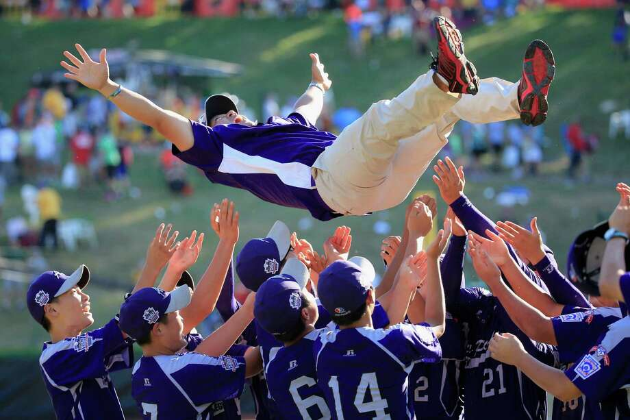 SOUTH WILLIAMSPORT, PA - AUGUST 24:  Members of Team Asia-Pacific (L) throw an assistant coach in the air following their 8-4 win over the Great Lakes Team from Chicago, Illinois to win the Little League World Series Championship game at Lamade Stadium on August 24, 2014 in South Williamsport, Pennsylvania.  (Photo by Rob Carr/Getty Images) ORG XMIT: 508283193 Photo: Rob Carr / 2014 Getty Images