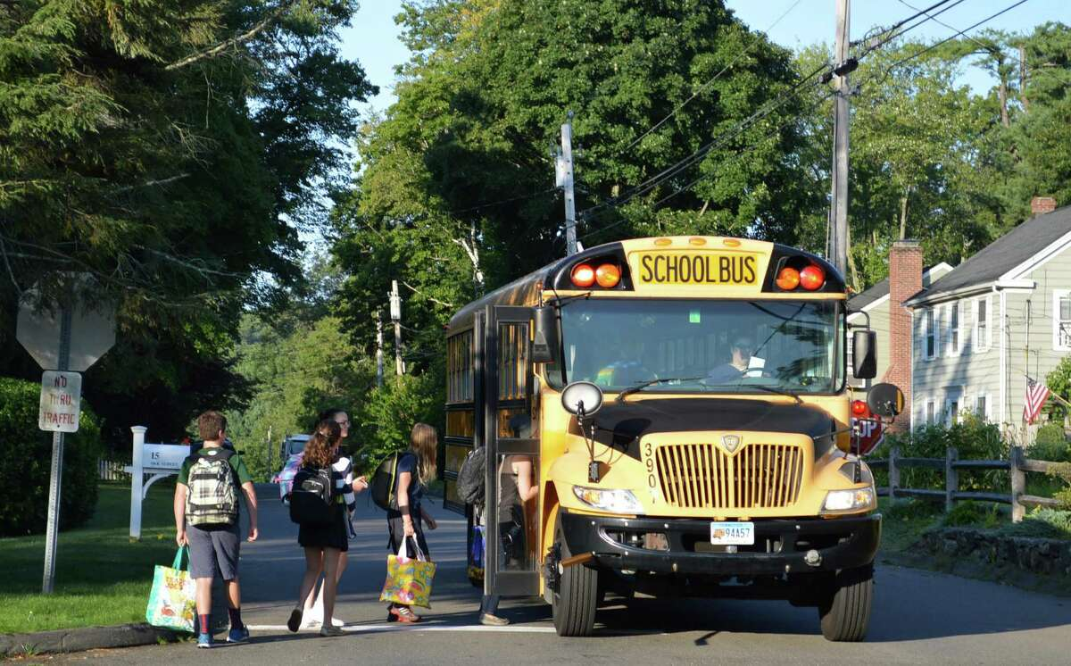 Students board a bus on Oak Street Monday morning for the first day of classes in the new academic year.