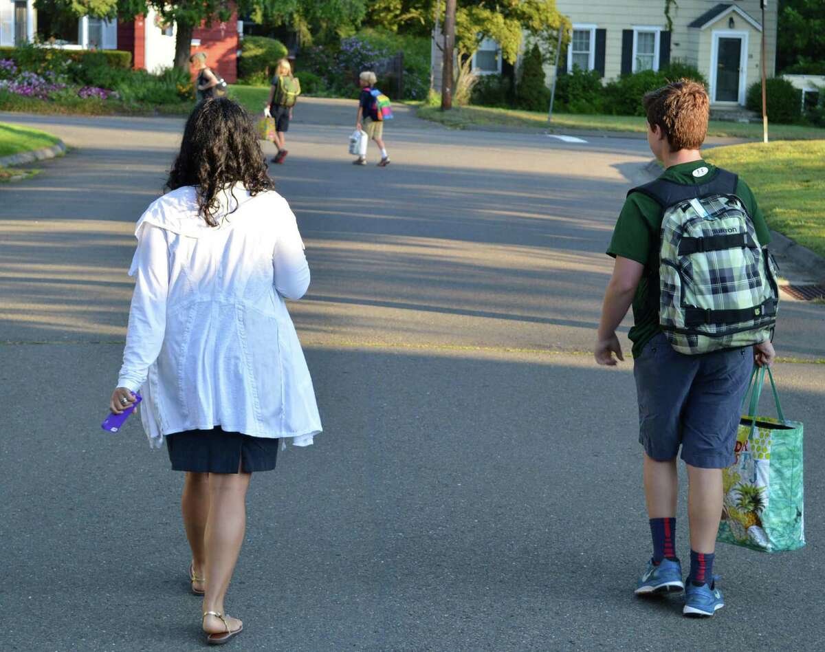 Jodi Robison and son Eli, 12, make their way to a bus stop Monday for the first ride of the new school year.