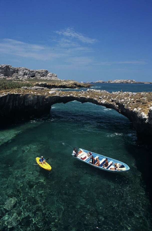 Tour boat and kayak explore a natural arch and cove at Las Islas Marietas. Photo: Mark D. Callanan / (c) Mark D Callanan