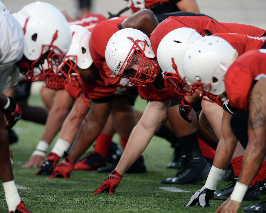The Cardinals defensive line sets up for a play during Thursday's practice. The Lamar Cardinals football team practiced at Provost Umphrey Stadium on Thursday evening. Photo taken Thursday 8/21/14 Jake Daniels/@JakeD_in_SETX Photo: Jake Daniels / ©2014 The Beaumont Enterprise/Jake Daniels