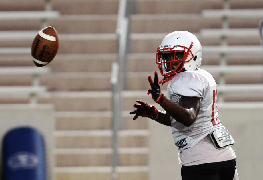 Lamar running back Carl Harris reaches out for a one-handed catch during practice Thursday. The Lamar Cardinals football team practiced at Provost Umphrey Stadium on Thursday evening.  Photo taken Thursday 8/21/14  Jake Daniels/@JakeD_in_SETX Photo: Jake Daniels / ©2014 The Beaumont Enterprise/Jake Daniels