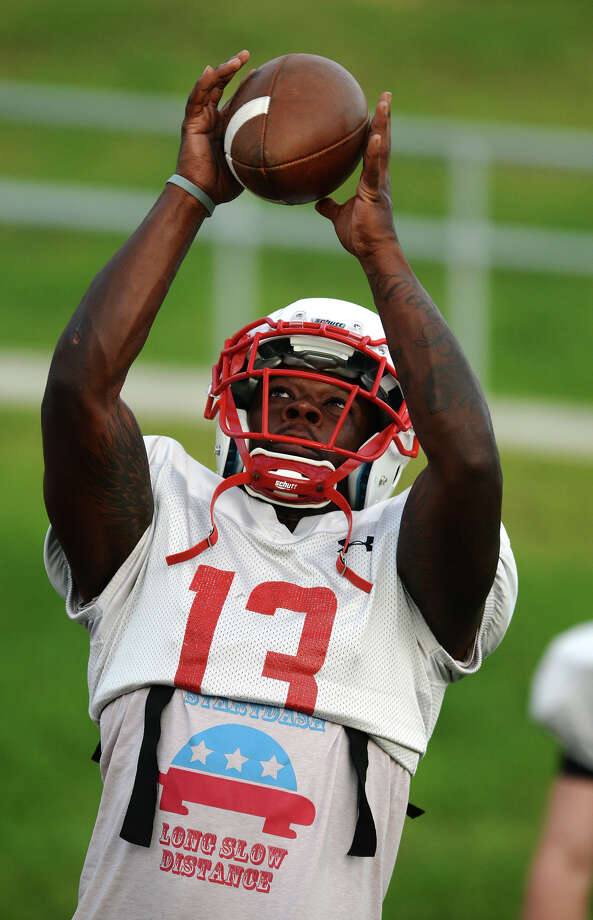 Lamar running back Carl Harris stretches up for a catch while warming up Thursday. The Lamar Cardinals football team practiced at Provost Umphrey Stadium on Thursday evening.  Photo taken Thursday 8/21/14  Jake Daniels/@JakeD_in_SETX Photo: Jake Daniels / ©2014 The Beaumont Enterprise/Jake Daniels