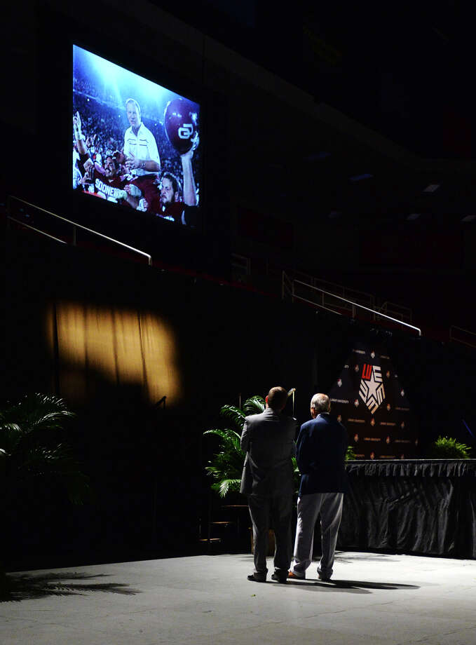 Lamar Athletics Director Jason Henderson, left, stands with former Oklahoma Sooners and Dallas Cowboys coach Barry Switzer as they watch a brief summary of Switzer's football career Sunday. The Lamar Cardinals held their annual kickoff celebration at the Montagne Center on Sunday evening. Switzer was the night's keynote speaker.  Photo taken Sunday 8/24/14 Jake Daniels/@JakeD_in_SETX Photo: Jake Daniels / ©2014 The Beaumont Enterprise/Jake Daniels