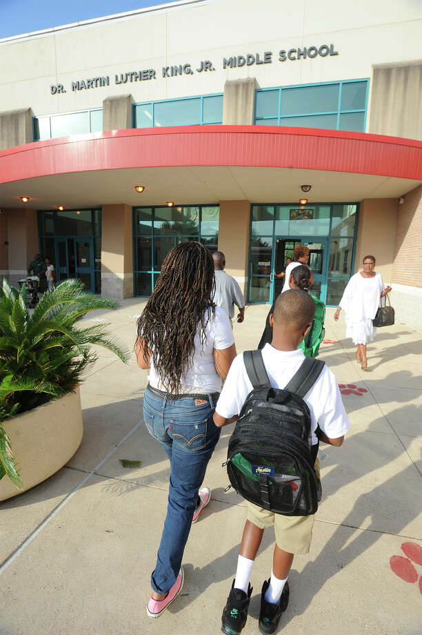 Tiffany Freeman walks Kameron Moore, 11, to his first day of sixth grade at Martin Luther King Junior High in Beaumont on Monday. Monday marked the first day that Austin Middle School students merged with MLK. Photo taken Monday, August 25, 2014 Guiseppe Barranco/@spotnewsshooter Photo: Guiseppe Barranco, Photo Editor