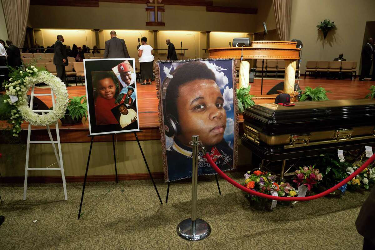 Photos surround the casket of Michael Brown before the start of his funeral at Friendly Temple Missionary Baptist Church in St. Louis, Monday, Aug. 25, 2014. Brown, who is black, was unarmed when he was shot in Ferguson, Mo., Aug. 9 by Officer Darren Wilson, who is white. Protesters took to the streets of the St. Louis suburb night after night, calling for change and drawing national attention to issues surrounding race and policing.