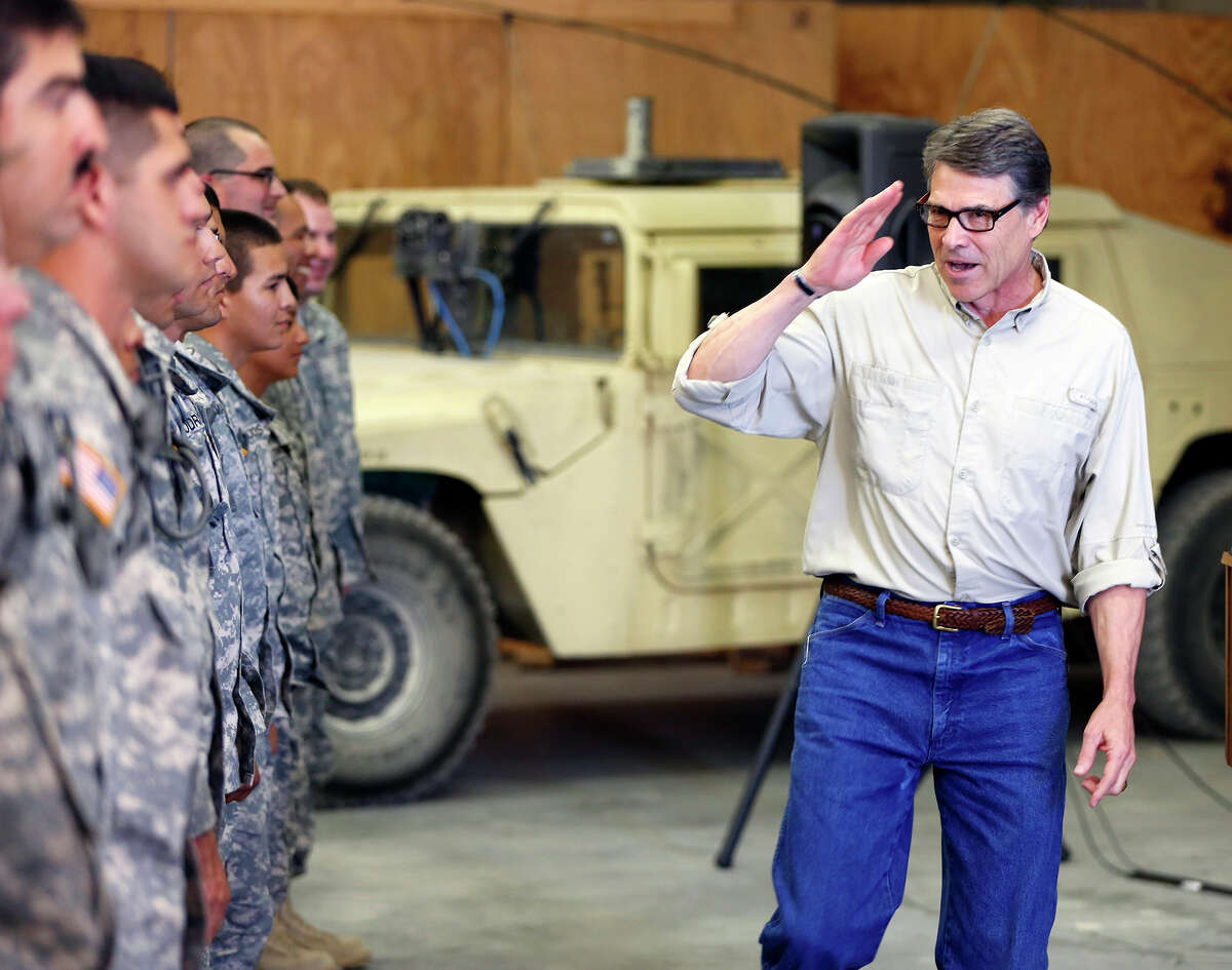 Gov. Rick Perry salutes National Guard troops at Camp Swift in Bastrop, Texas on Wednesday, Aug. 13, 2014 after talking to them about their upcoming mission along the Texas border. Perry visited some of the 1,000 troops he has ordered to the Texas-Mexico border but says he does not know how long they'll be deployed. (AP Photo/San Antonio Express-News, William Luther)