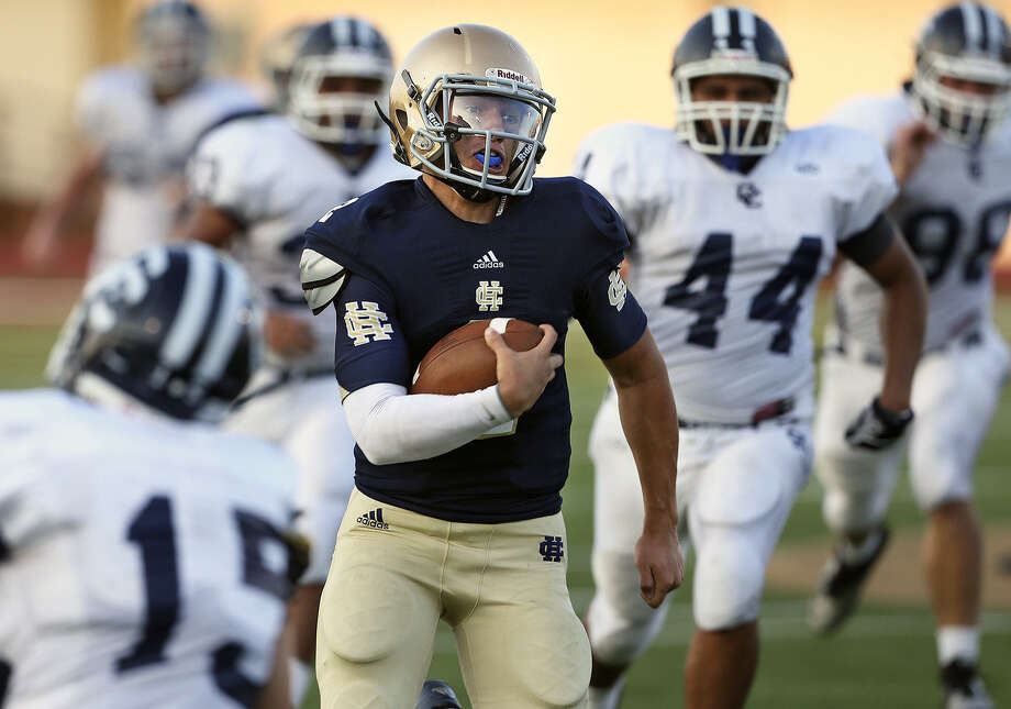 Knight quarterback Cisco Flores turns on the speed to outrun Button defenders and score in the first half of the 2013 Holy Bowl, which features rivals Holy Cross and Central Catholic. Photo: Tom Reel / Express-News File Photo