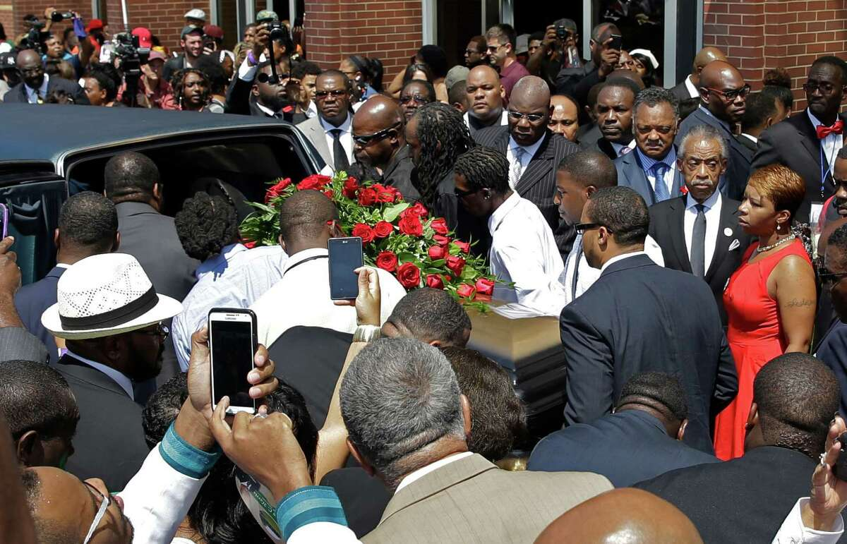 People gather outside of Friendly Temple Missionary Baptist Church as Michael Brown's mother Lesley McSpadden, right, Rev. Al Sharpton, and Rev. Jesse Jackson follow the casket during the funeral for Michael Brown Monday, Aug. 25, 2014, in St. Louis. Brown, a black 18-year-old who was unarmed, he was shot Aug. 9 by Officer Darren Wilson, who is white. A grand jury is considering evidence in the case and a federal investigation is also underway.