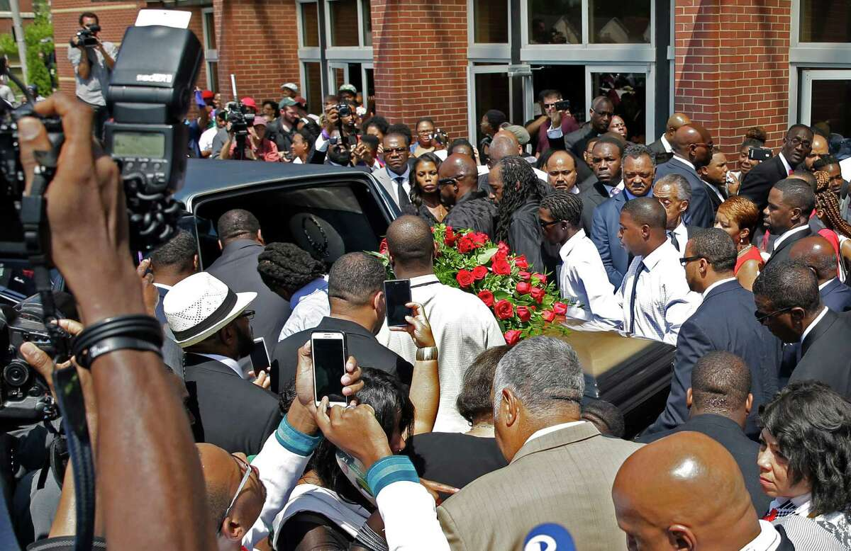 The casket of Michael Brown is carried to a hearse after the funeral service for Michael Brown Monday, Aug. 25, 2014, in St. Louis. Brown, a black 18-year-old who was unarmed, he was shot Aug. 9 by Officer Darren Wilson, who is white. A grand jury is considering evidence in the case and a federal investigation is also underway.