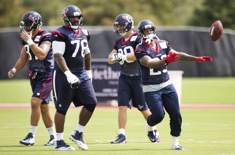 Houston Texans running back Arian Foster (23) flips a ball to a coach after running a play during Te