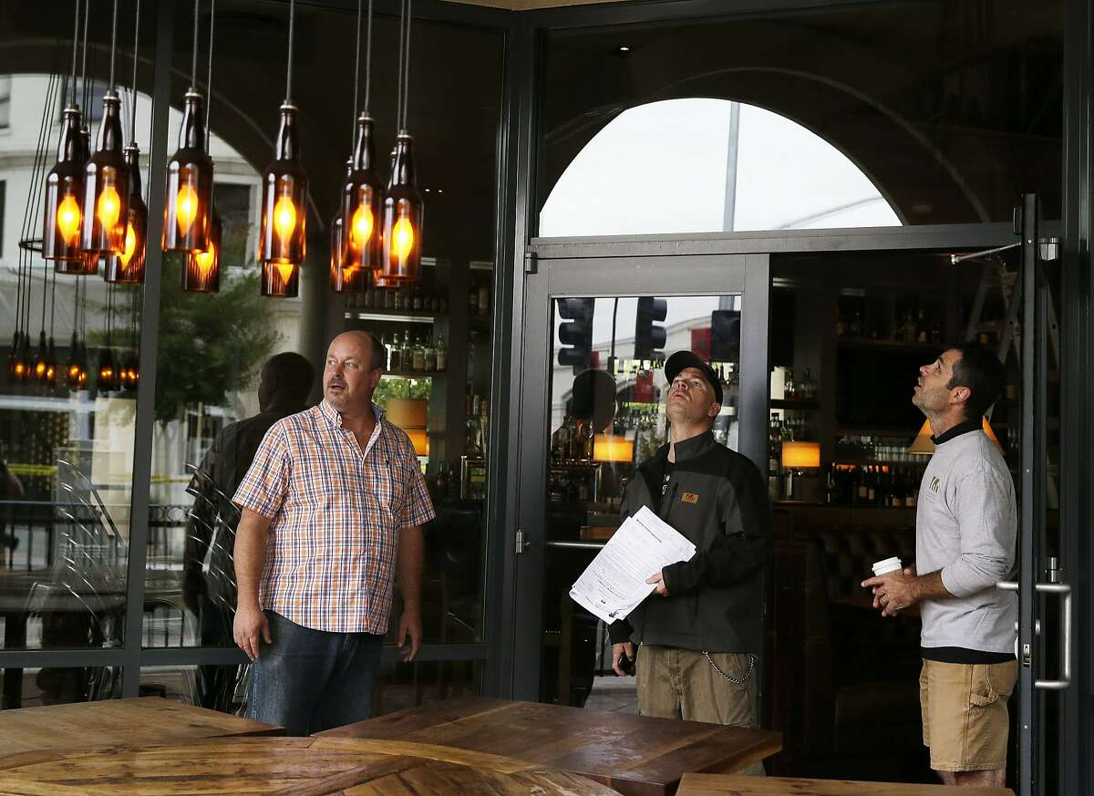 Jon Crane, left, manager of the Norman Rose tavern stands with contractors Bryn Sloan, center, and Paul Niles, as they look for earthquake damage Monday, Aug. 25, 2014, in Napa, Calif. The San Francisco Bay Area's strongest earthquake in 25 years struck the heart of California's wine country early Sunday, igniting gas-fed fires, damaging some of the region's famed wineries and historic buildings, and sending dozens of people to hospitals. (AP Photo/Eric Risberg)