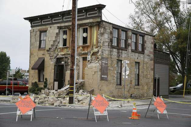 Signs and caution tape block the street in front of the earthquake-damaged Vintner's Collective multi-winery tasting room Monday, Aug.