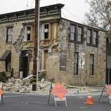 Signs and caution tape block the street in front of the earthquake-damaged Vintner's Collective multi-winery tasting room Monday, Aug. 25, 2014, in Napa, Calif. The building dates from the late 1800s. The San Francisco Bay Area's strongest earthquake in 25 years struck the heart of California's wine country early Sunday, igniting gas-fed fires, damaging some of the region's famed wineries and historic buildings, and sending dozens of people to hospitals.