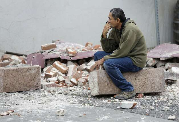 Ron Peralez, of Vacaville, Calif., sits on rubble and looks at earthquake-damaged buildings Monday, Aug. 25, 2014, in Napa, Calif. The San Francisco Bay Area's strongest earthquake in 25 years struck the heart of California's wine country early Sunday, igniting gas-fed fires, damaging some of the region's famed wineries and historic buildings, and sending dozens of people to hospitals. Photo: Eric Risberg, Associated Press