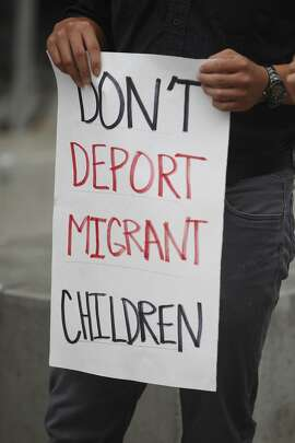 A demonstrator holds a sign during a press conference at the San Francisco Federal Building where immigrant rights groups gathered to demand recognition for children refugees entering the United States on Monday, July 21,  2014 in San Francisco, Calif.