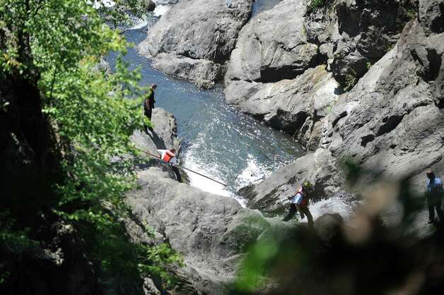 Rescuers use a long pole with a hook to search the water as they search for a man who went missing in the Poestenkill Gorge on Monday, Aug. 25, 2014, in Troy, N.Y.  (Paul Buckowski / Times Union) Photo: Paul Buckowski / 00028328A