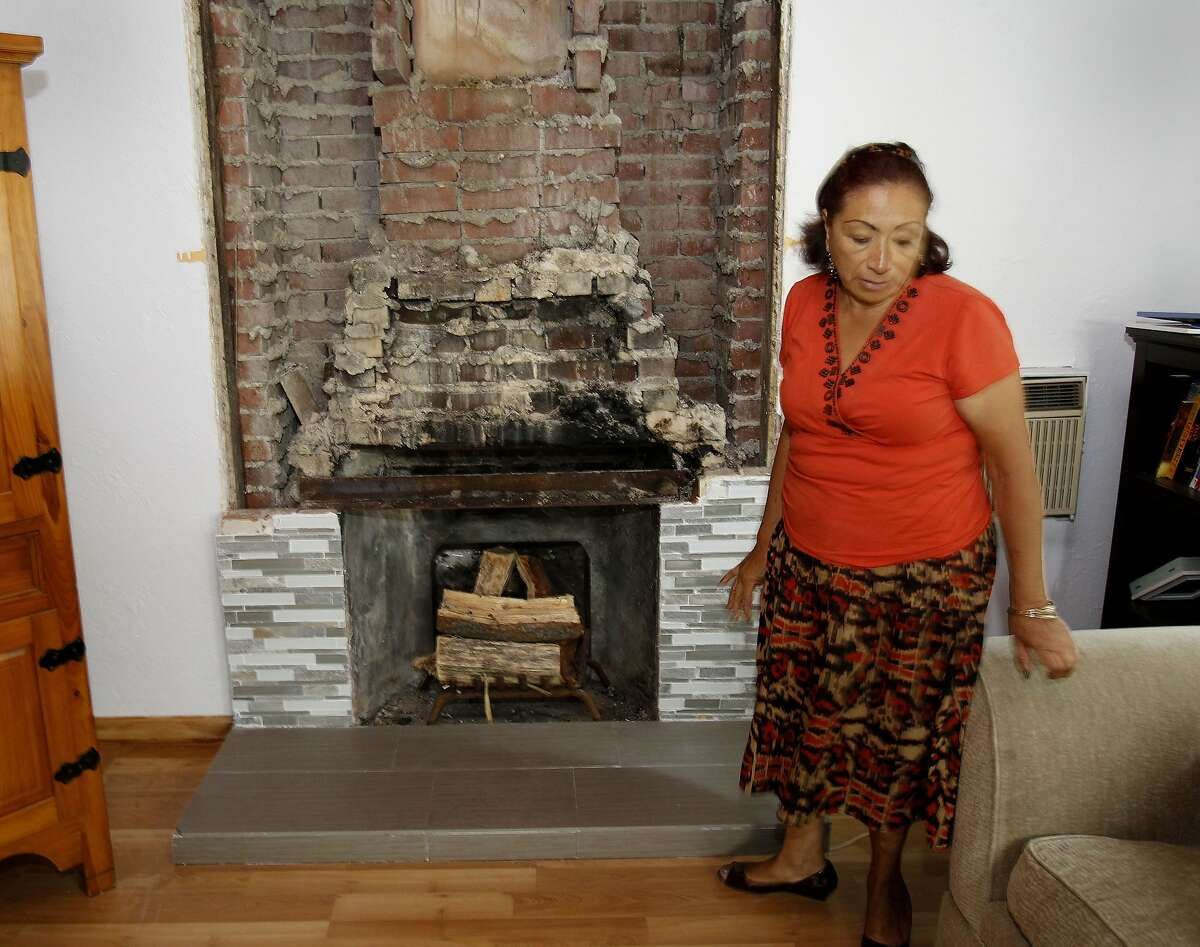Mrs. Rosales, a relative of Nicolas Dillon pauses near the fireplace where the bricks falling caused serious injury to the boy in Napa, Calif. The day after a strong earthquake hit the Napa Valley, residents and officials began to access the damage.