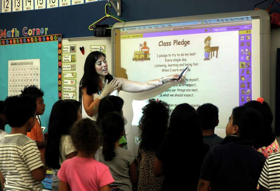 Caitlin Palinkas leads her first-grade class in the school pledge at Ellsworth Avenue School on the first day of school Monday, August 25, 2014. Photo: Carol Kaliff / The News-Times