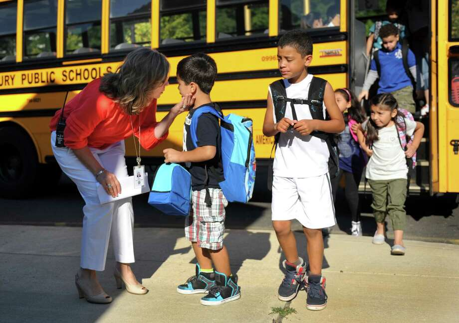Leandro Pacheco, 5, talks with principal Dr. Anna Rocco as he arrives at school for the first day of classes Monday, August 25, 2014, at Ellsworth Avenue School in Danbury, Conn. Photo: Carol Kaliff / The News-Times