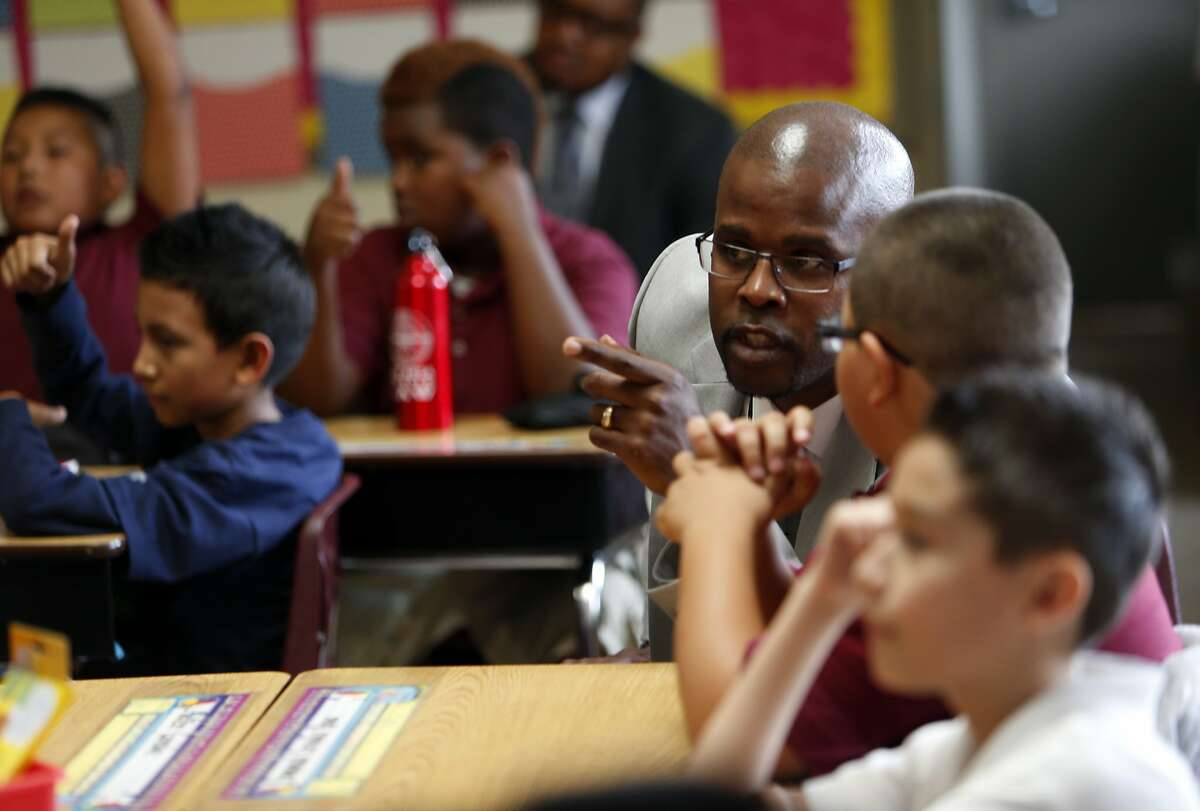 New Oakland Unified School District Superintendent Antwan Wilson asks 5th grader Emmanuel Cervantes Rivas, 9, a question on first day of school at Think College Now in Oakland, Calif. on Monday, August 25, 2014.