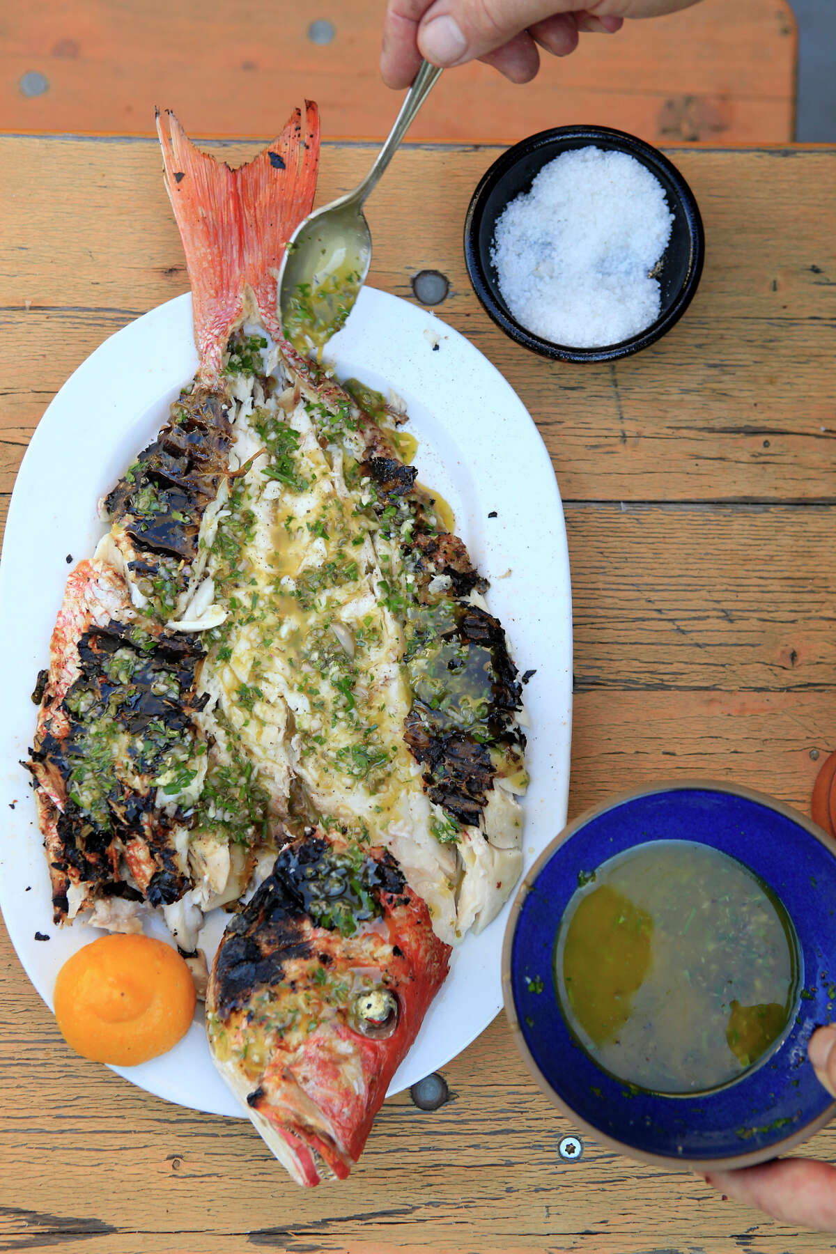 Chef Erik Cosselmon dresses the fish with a lemon vinaigrette, at his home in San Francisco, CA, Wednesday, August 12, 2014.