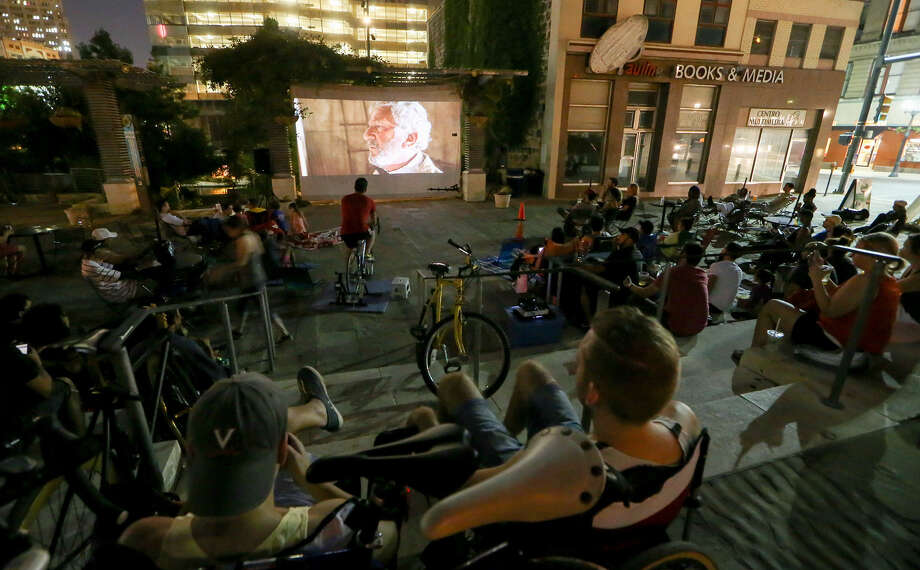 """Kyle Moller (center) powers the generator for a recent showing of """"The Fifth Element"""" at Cycle-In Cinema in Main Plaza. Photo: Photos By Marvin Pfeiffer / EN Communities / EN Communities 2014"""