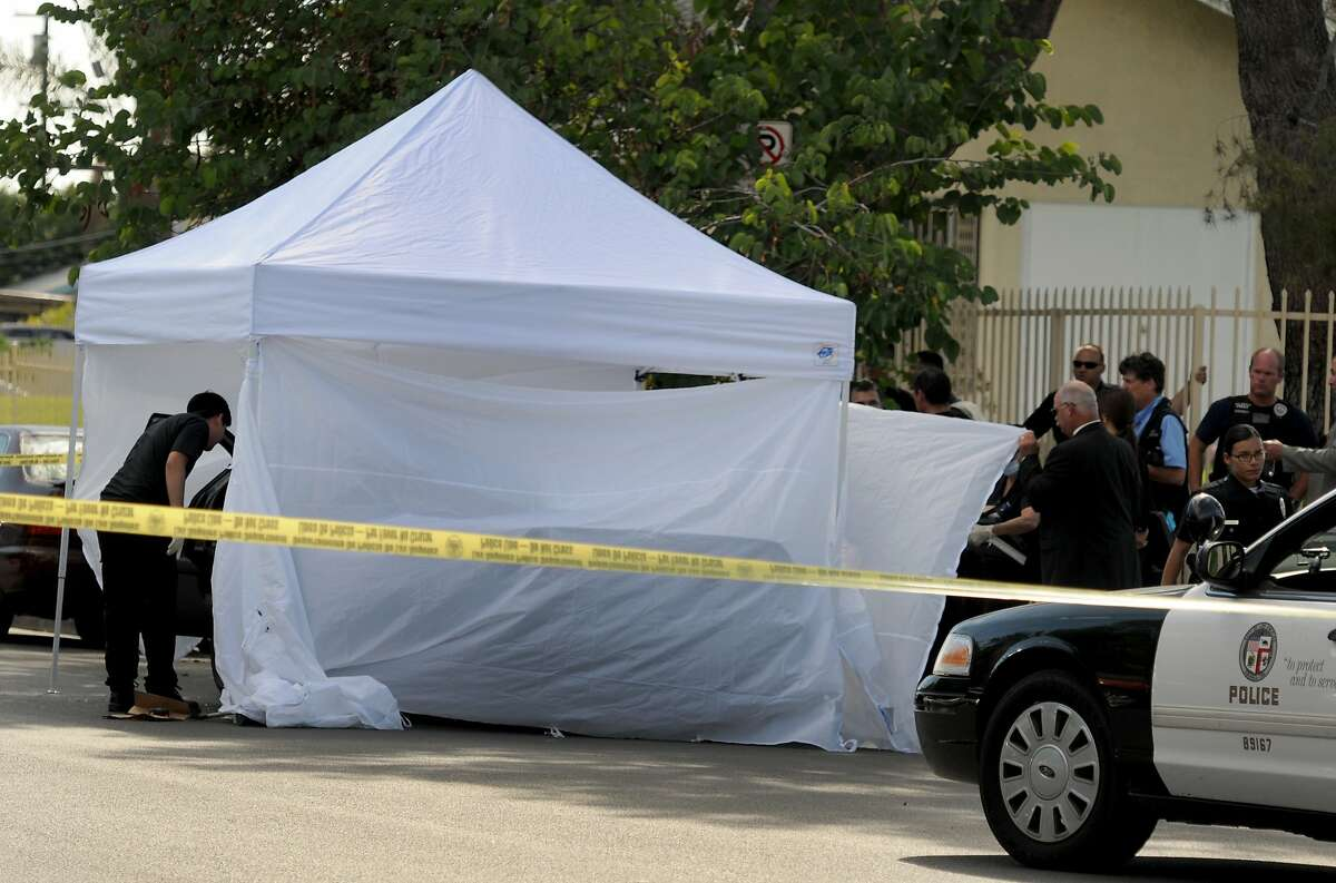 Los Angeles Police Department officers investigate the scene of a shooting Sunday, Aug. 24, 2014, where one person was killed near the 14400 block of Polk Street in Sylmar, Calif. Describing what they called