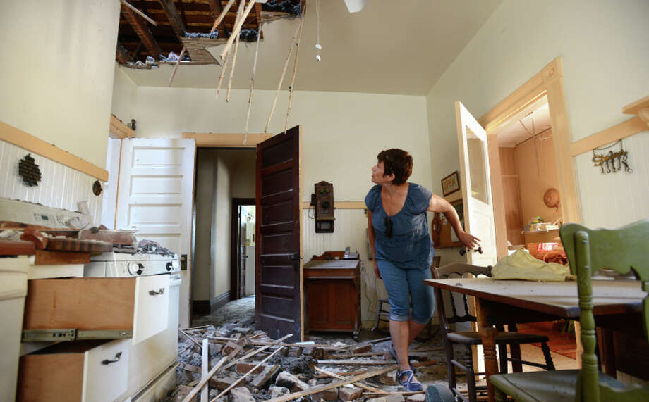 "Kelly Darter looking over damage from the chimney that came crashing into the kitchen of her home on the 1600 block of First Street in downtown Napa after Sunday morning's 6.0 quake. ""Oh yeah, we've decided, we're going to fix this,"" said Darter whose family built the home in 1905 after arriving from Prussia and whose 97-year-old grandmother Claire Erks just passed away last September in the next room. August 25, 2014. Photo: Erik Castro / Special To The Chronicle / ONLINE_YES"