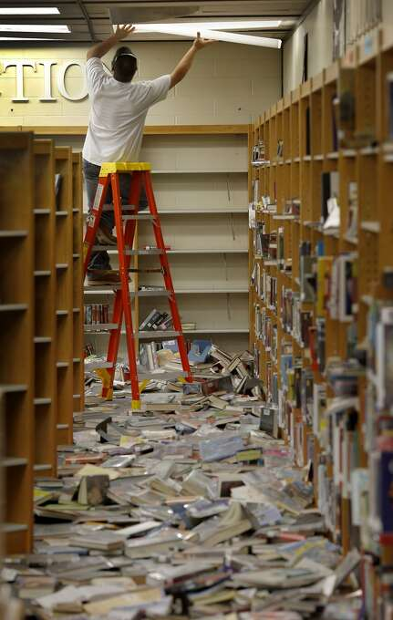 An electrician first worked on the fallen lights before the books could be picked up at the Napa High School. Officials at Napa High School will decide whether classes can resume after cleaning up many of the classrooms Monday August 26, 2014. Photo: Brant Ward, San Francisco Chronicle
