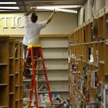 An electrician first worked on the fallen lights before the books could be picked up at the Napa High School. Officials at Napa High School will decide whether classes can resume after cleaning up many of the classrooms Monday August 26, 2014.