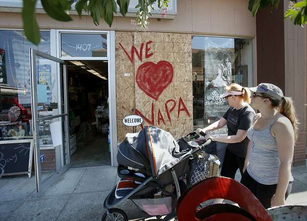Two women pass a newly reopened store on Second Street advertising their love for Napa. Residents and shop owners in Napa, Calif. spent the day cleaning up or moving out after the large earthquake Sunday. Photo: Brant Ward, San Francisco Chronicle