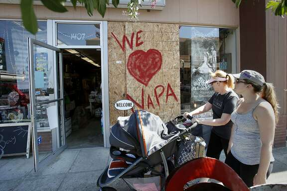 Two women pass a newly reopened store on Second Street advertising their love for Napa. Residents and shop owners in Napa, Calif. spent the day cleaning up or moving out after the large earthquake Sunday.