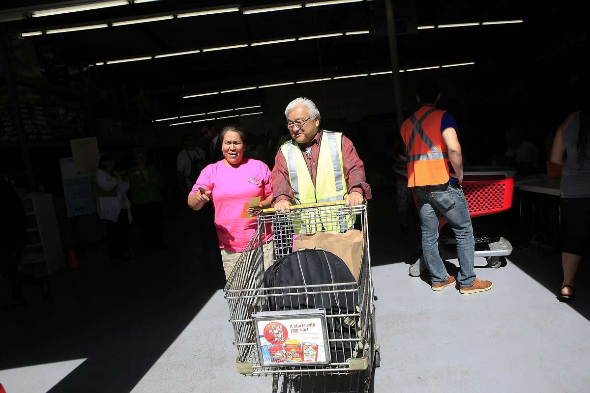 Rep. Mike Honda pushes a cart for Guadalupe Garcia as she visits the Sunnyvale Community Services building for a back-to-school backpack and food giveaway, in Sunnyvale, CA, Thursday, August 14, 2014.