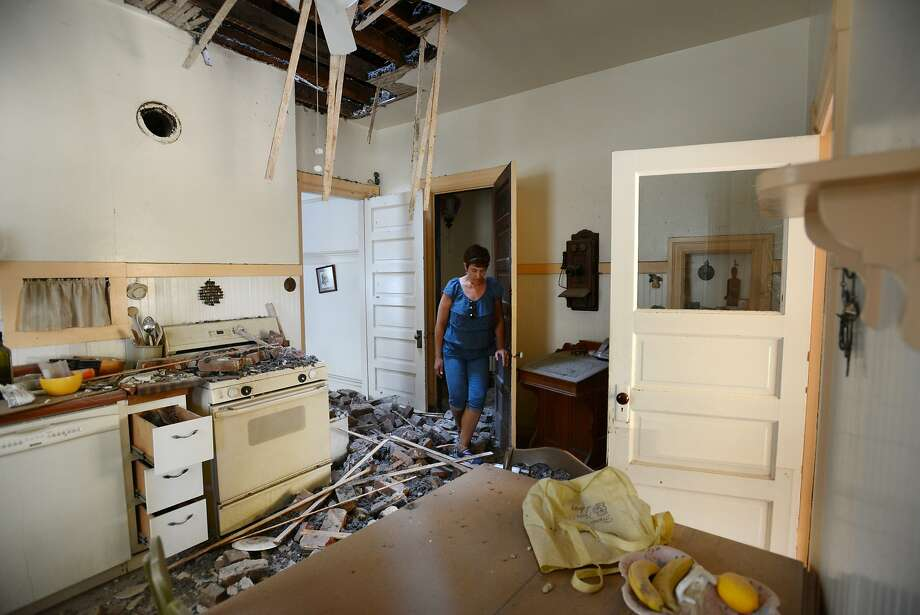 "Kelly Darter looking over damage from the chimney that came crashing into the kitchen of her home on the 1600 block of First Street in downtown Napa after Sunday morning's 6.0 quake. ""Oh yeah, we've decided, we're going to fix this,"" said Darter whose family built the home in 1905 after arriving from Prussia and whose 97-year-old grandmother Claire Erks just passed away last September in the next room. August 25, 2014. Photo: Erik Castro, Special To The Chronicle"