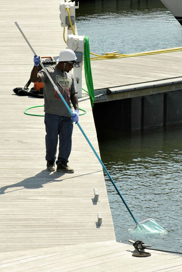 A construction contractor working on the Washington Boulevard tower developed by Building and Land Technology in the city's South End fishes debris out of the West Branch of Stamford Harbor in Stamford, Conn., on Monday, Aug. 25, 2014. The tower's styrofoam insulation allegedly blew off the building and into the water. Photo: Jason Rearick / Stamford Advocate