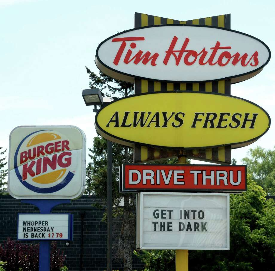 A Burger King sign and a Tim Hortons sign are displayed in Ottawa, Ontario, Monday, Aug. 25, 2014. Burger King is in talks to buy Tim Hortons in hopes of creating a new, publicly traded company with its headquarters in Canada. (AP Photo/The Canadian Press, Sean Kilpatrick) ORG XMIT: OTTK102 Photo: Sean Kilpatrick / The Canadian Press
