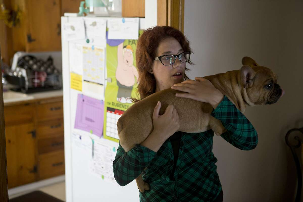Kayla Bernardy holds her sister's dog. Ozze, while walking through her sister's damaged home near the corner of Fern Place and Tennessee Street on Monday, August 25, 2014 in Vallejo, Calif.