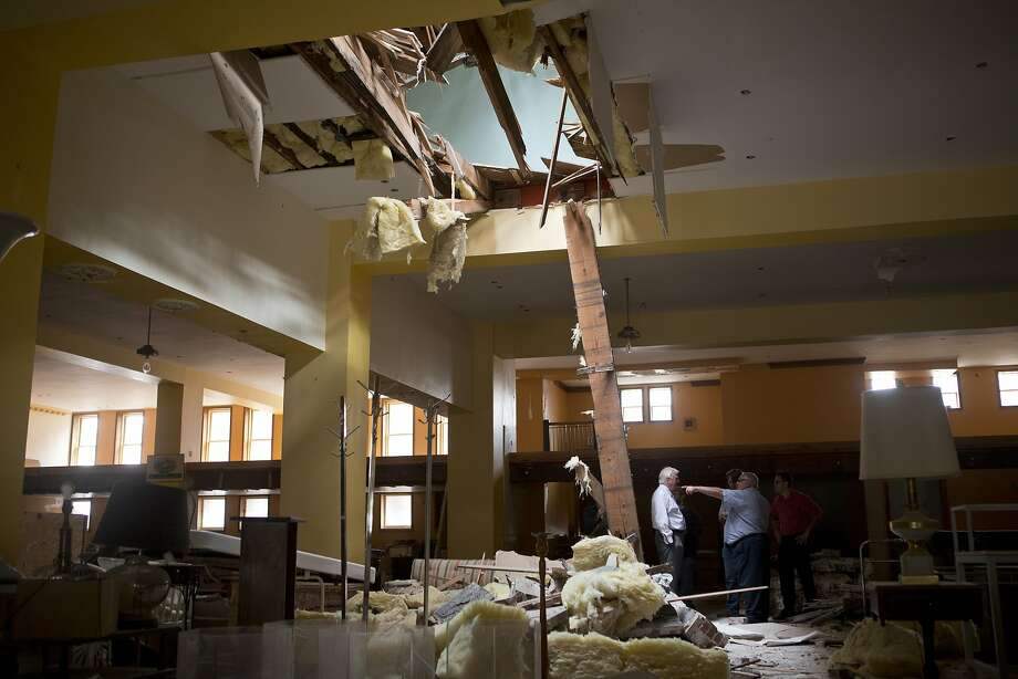 Rep. Mike Thompson (left) and property owner Buck Kamphausen discuss how falling masonry tore through the ceiling and second floor of a Vallejo building. Photo: Beck Diefenbach, Special To The Chronicle
