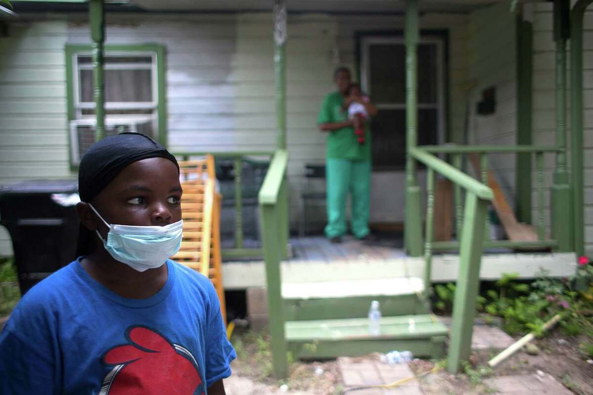 Daymon Thomas, 7, says he can smell the chemicals at the abandoned hazardous waste site from the front yard of his home in south Houston.