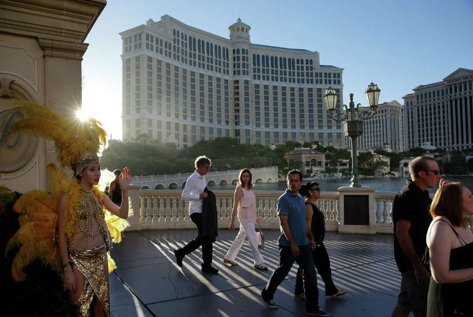 In this Friday, Aug. 15, 2014 photo, people walk by the Bellagio, in Las Vegas. This year, hotels will take in a record $2.25 billion in revenue from fees and surcharges, 6 percent more than in 2013 and nearly double that of a decade ago, according to a new study. Nearly half of the increase can be attributed to new surcharges and hotels increasing the amounts of existing fees. (AP Photo/John Locher) ORG XMIT: NYBZ213 Photo: John Locher / AP