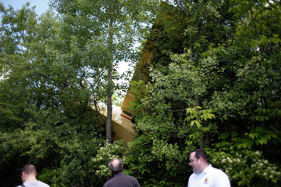 Safety workers investigate the replica 1949 Piper Clipper owned by Fred Jackson, 75, of Niskayuna, which was found hanging in a tree Saturday, July 21, 2014, in Altamont , N.Y. Jackson overshot the runway and crashed into trees on Gray Road at about 12:30 p.m. on June 14. He walked away with only a scratch, but didn't report the incident to the Federal Aviation Administration. There were no passengers. A week later the land owners found the wreck and reported it to Guilderland town police. (Tom Brenner/Special to the Times Union) Photo: Tom Brenner / ©Tom Brenner/ Albany Times Union
