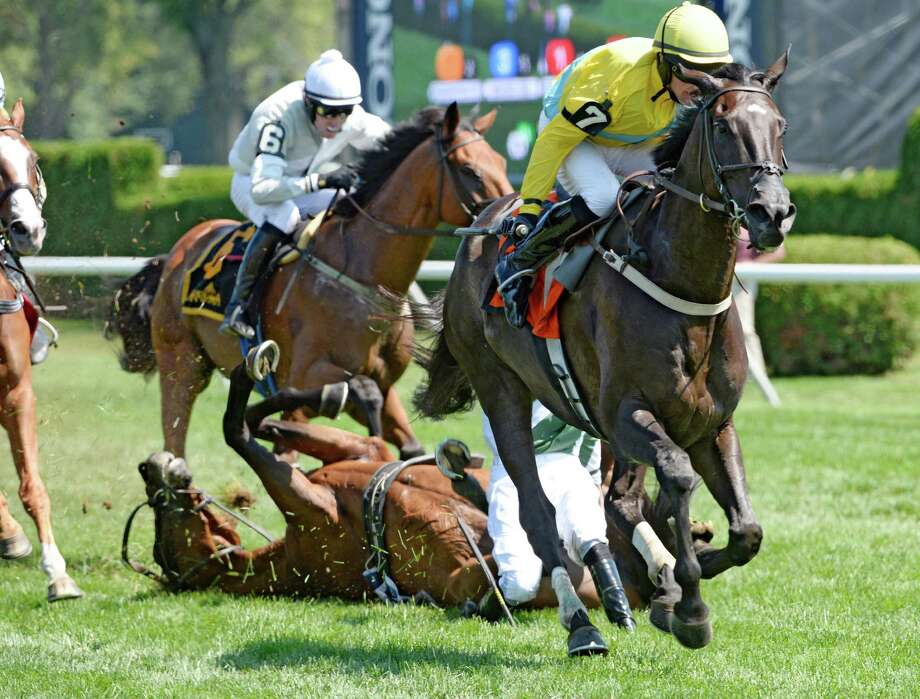 #7 Demonstrative, right, with jockey Robert Walsh runs on after the final fence with the ill-fated #3 Makari falling with jockey Jack Doyle in the 73rd running of the New York Turf Writers Cup Aug, 25, 2014, at Saratoga Race Course in Saratoga Springs, N.Y.  Makari lost his footing on the other side of the fence and unseated the rider as he went to the ground. He did not get up.  (Skip Dickstein/Times Union) Photo: SKIP DICKSTEIN