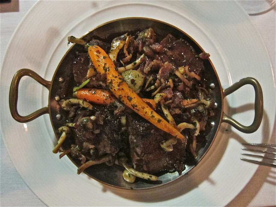 """Boeuf bourguignon (BOOF boor-gee-NYON):Hard to spell, much less pronounce, a classic French dish of beef braised in red wine and onions, and topped with sauteed mushrooms. Audio: Click here to hear the term """"Boeuf bourguignon."""" Photo: Alison Cook"""