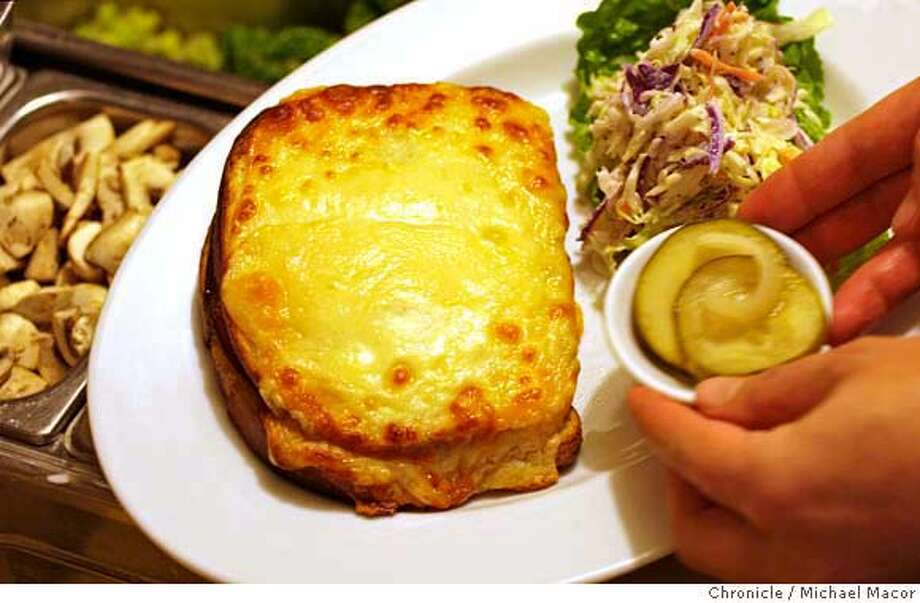 """Croque Monsieur (CROAK muhs-YOOR):A grilled ham and cheese sandwich, usually made with Swiss or Gruyère, that's dipped in beaten eggs before being grilled. Audio: Click here to hear the term """"Croque Monsieur."""" Photo: Michael Macor"""