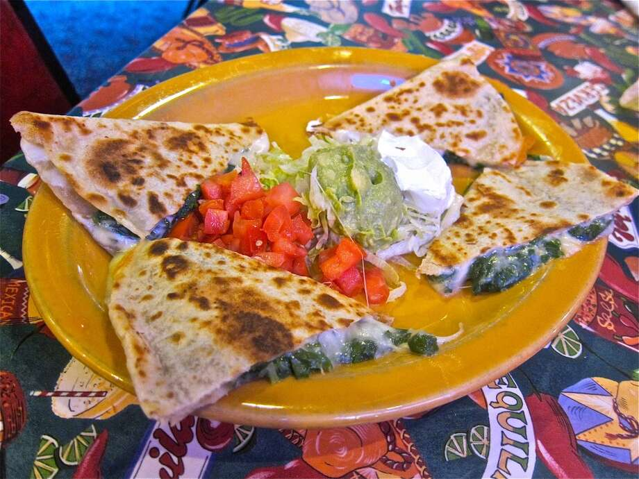 "Quesadilla (keh-sah-DEE-yah): Don't pull a Napolean Dynamite and pronounce a hard L for this dish of two flour tortillas grilled and filled with melted cheese and other items. Audio: Click here to hear the term ""Quesadilla."" Photo: Alison Cook"