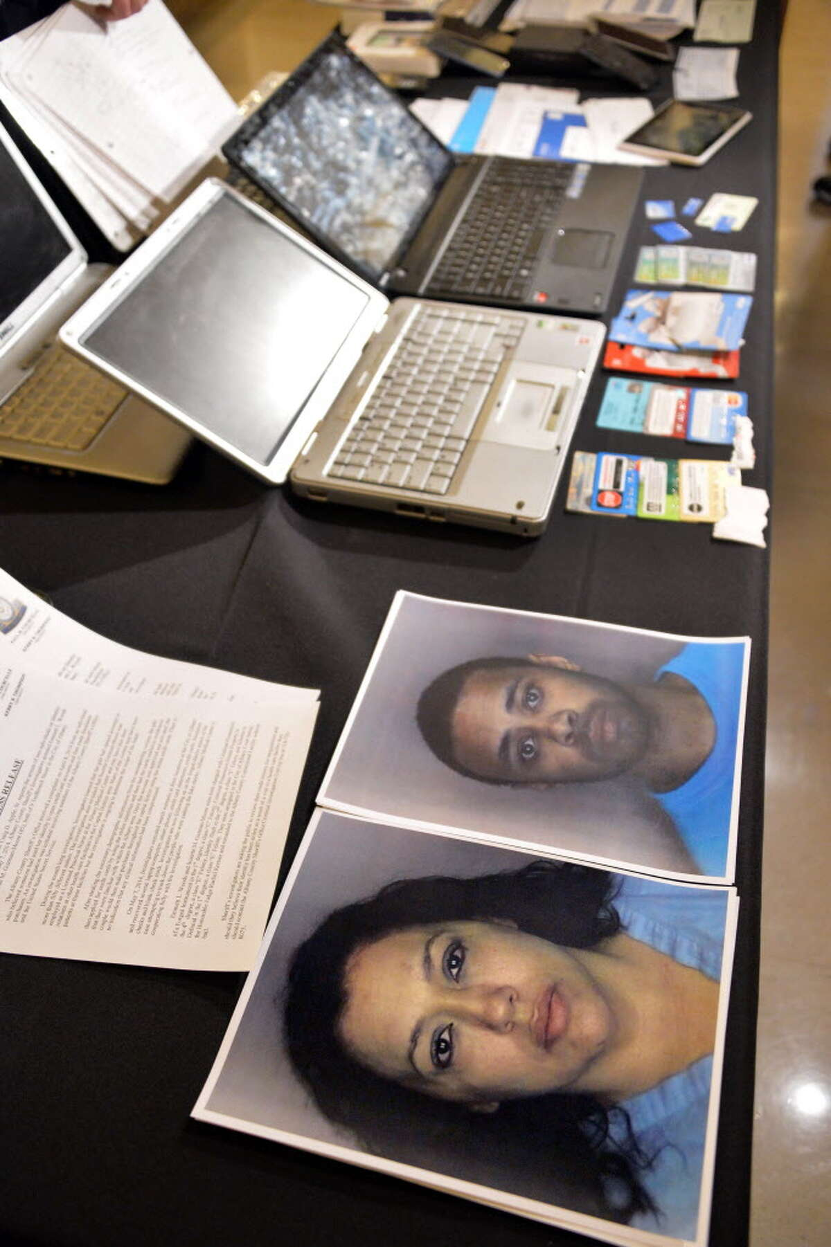 Albany Co. Sheriff Dept. photos of Suzette M. Guzman-Moore, bottom, and Emmett L. Woods on a table full of evidence at the announcement of their arrest on Identity Theft charges during at news conference Thursday May 8, 2014, in Albany, NY. (John Carl D'Annibale / Times Union)