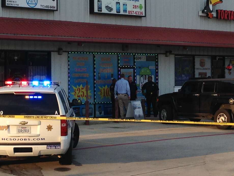 Authorities suspect the shooting outside a Fiesta grocery store is related to robbery at a nearby cell phone store on Monday. Photo: Mike Glenn, Chronicle