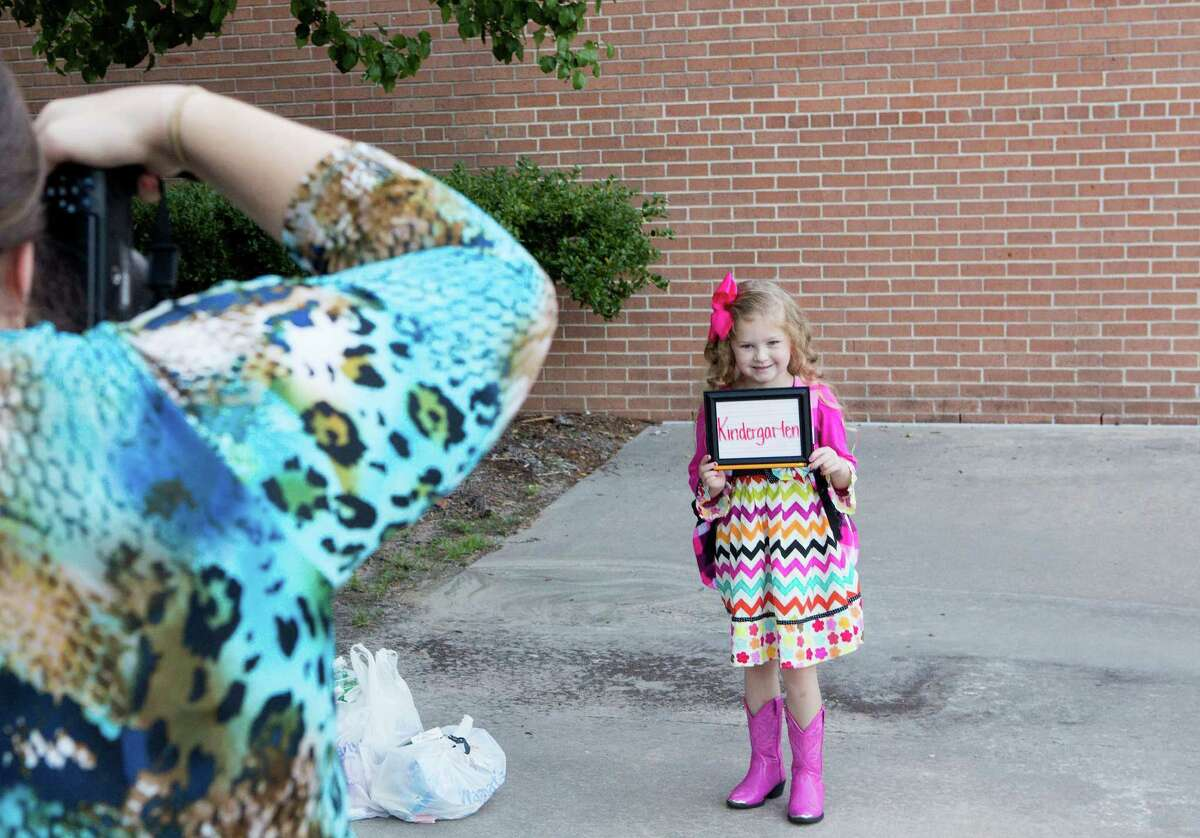 Breely Hobbs, 5, holds a sign for a photo Monday on her first day at Powell Elementary in The Woodlands.